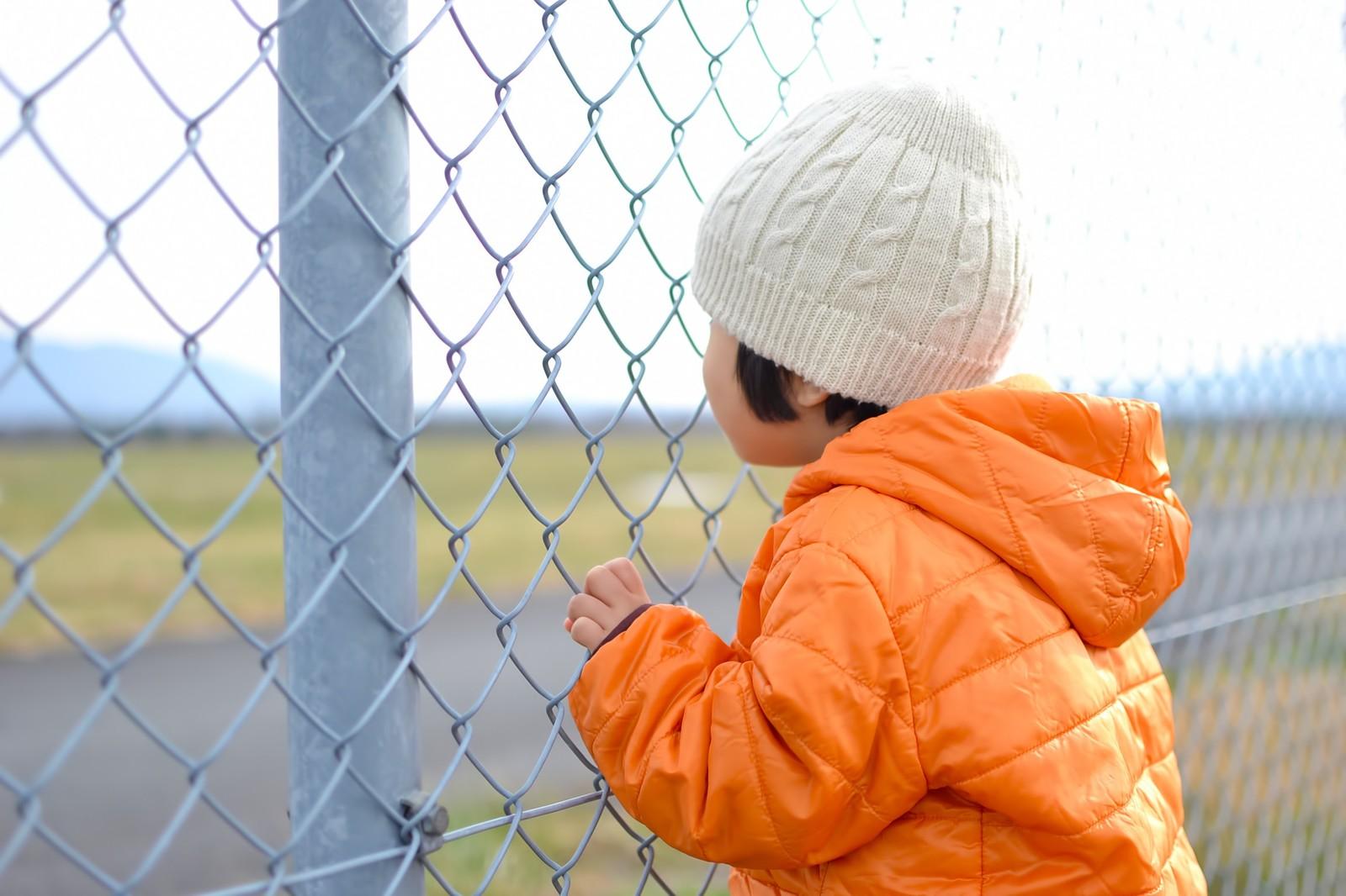子供とフェンスがフェンスにしがみつく写真