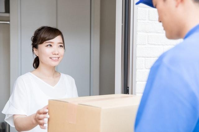 郵便物を受け取る女性