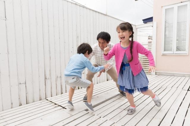 親子で元気にフェンスのあるウッドデッキで遊ぶ様子
